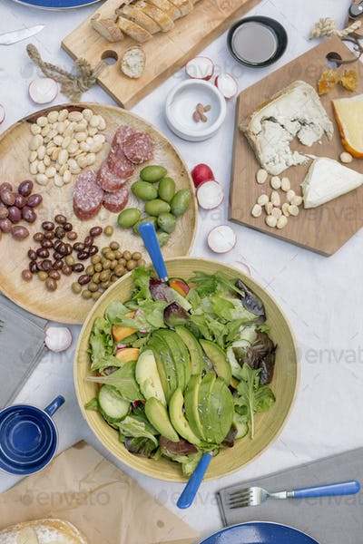 High angle view of a cheese board, cheese, olives, nuts and a bowl of salad on a table.
