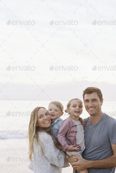 Couple standing with their son and daughter on a sandy beach by the ocean, smiling at camera.