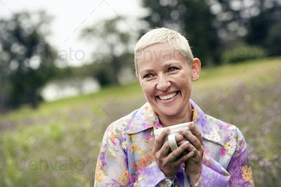 A woman with her hands wrapped around a coffee cup, sitting on a meadow.