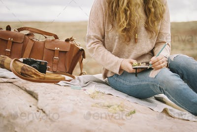 Woman sitting on a rock holding a notebook and pencil, a leather bag and camera lying beside her.