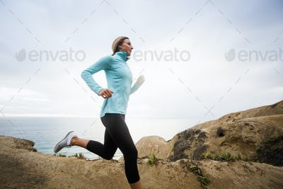 A young woman jogging along the coast.