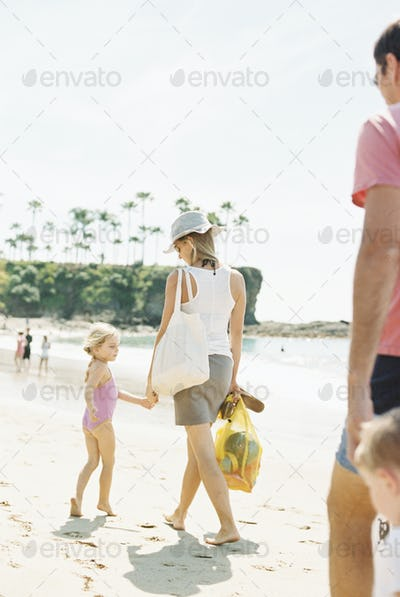 Family on a day out at a sandy beach by the ocean.