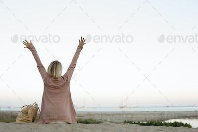 Blond woman sitting on a sandy beach, arms raised.