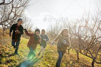 Four children running outdoors in winter