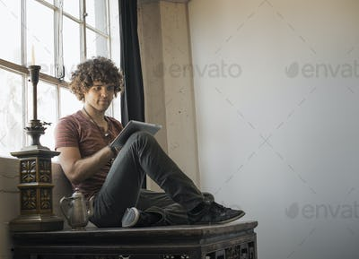 Loft living. A man sitting by a window using a digital tablet.