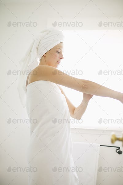 Woman wrapped in a white towel standing in a bathroom, applying lotion to her arm.