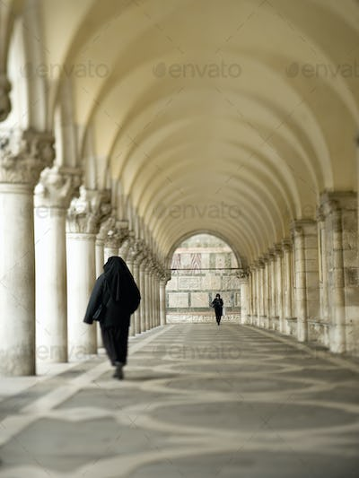 Piazza San Marco arcades and a series of columns. Two people walking.