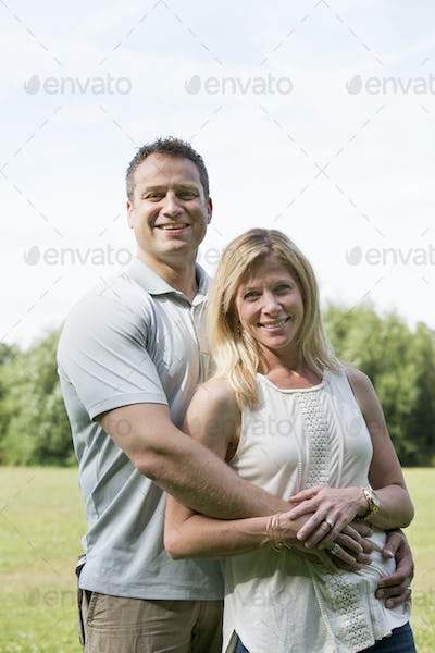 A couple, a man and woman standing in a park, smiling and embracing.