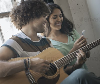 A young man playing guitar and a woman beside him taking photographs with a smart phone.