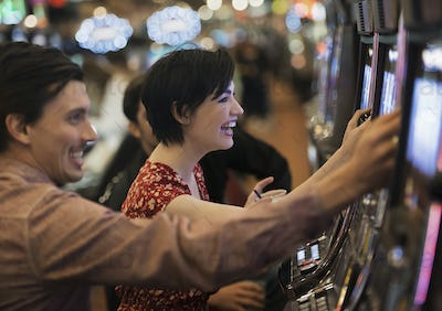 Two people, a young man and woman, playing the slot machines in a casino.
