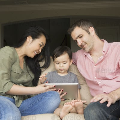 Smiling couple sitting on a sofa with their young son, looking at a digital tablet.