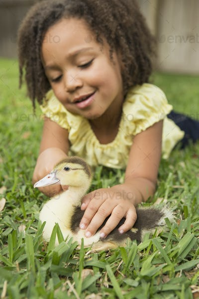 A girl petting a small duckling.