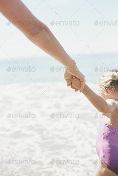 Woman and her daughter holding hands, standing on a sandy beach by he ocean.