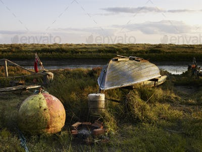 An upturned fishing boat by a narrow water channel in a flat landscape. Fishing floats and buoys.