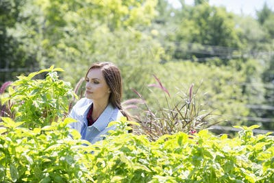A young woman standing in a garden surrounded by growing shrubs.