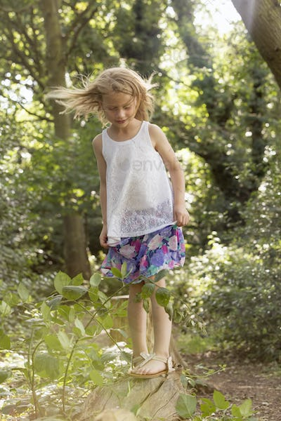 Young girl playing in a forest.