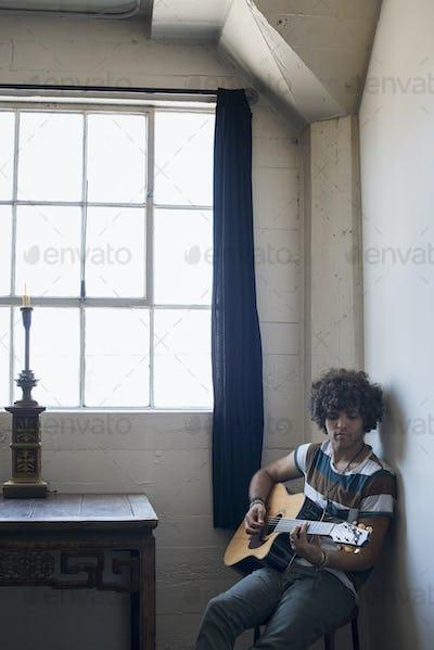 Loft living. A young man playing guitar.