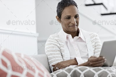 A woman seated using a digital tablet.