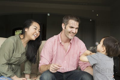 Smiling man and woman sitting side by side on a sofa, playing with their young son.