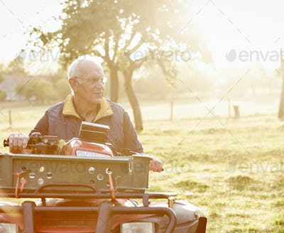 A farmer sitting on a quad bike in a field surveying his land.