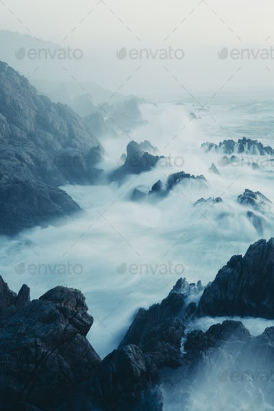 The Pacific Ocean coastline, with waves crashing against the shore.