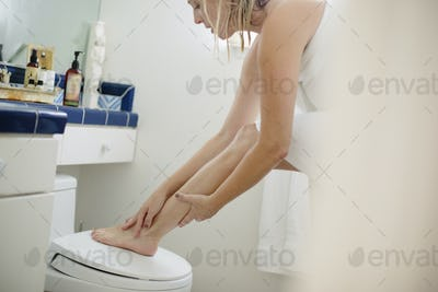 Woman wrapped in a white towel standing in a bathroom, applying lotion to her leg.