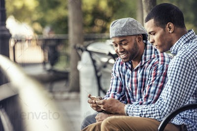 Two men sitting in a park, looking at a smart phone
