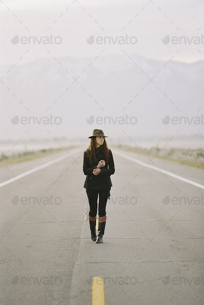 A woman walking down the middle of a country road, wearing a hat and carrying a backpack.