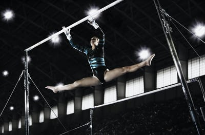 A gymnast, a young woman performing a routine on the parrallel bars.