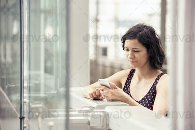 A woman standing outdoors checking her cell phone.