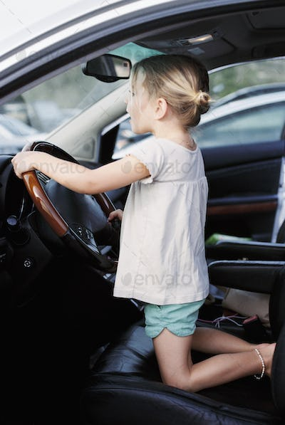Young girl kneeling on the drivers seat of a car, holding the steering wheel, pretending to drive.