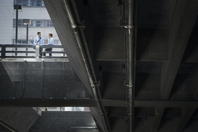 Two businessmen standing leaning on a railing on a city walkway, view from below.