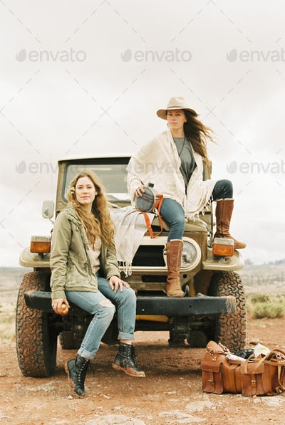 Two women sitting on the front of a jeep, on a road trip.