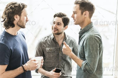 Three men standing talking, one with a cup of coffee, one with a smart phone.