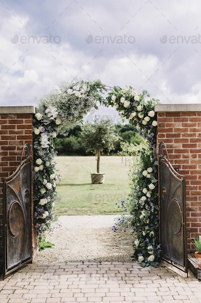 A door in a wall, and a white rose arch in a garden, with a view to a sundial.