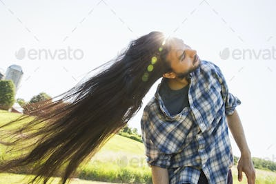 A young man shaking out his very long dark hair.