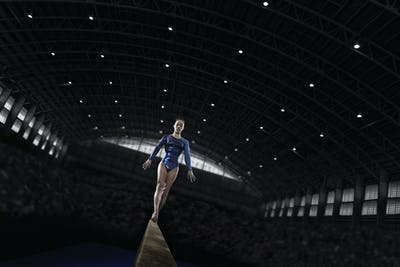 A young woman gymnast performing on the beam, balancing on a narrow piece of apparatus.