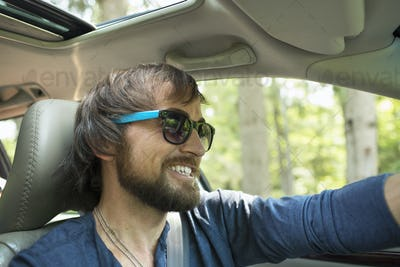 A man in sunglasses in the driving seat of a car.