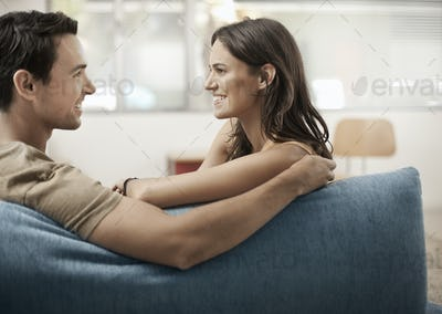 A young couple sitting on a sofa, gazing at each other, a man and woman, boyfriend and girlfriend.