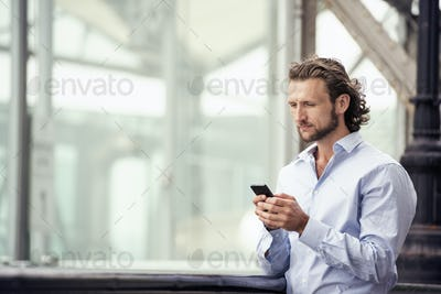 A man standing outdoors on the street, checking his cell phone.