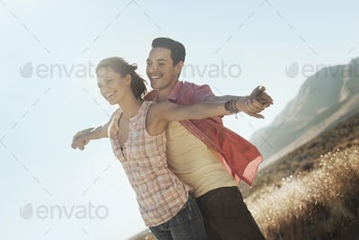A couple standing close together, arms outstretched leaning into the breeze, in open country.