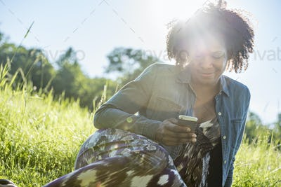 A woman sitting outdoors checking her smart phone.