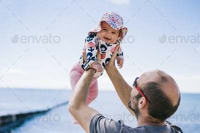 A father lifting his baby daughter in a sun bonnet up in the air,