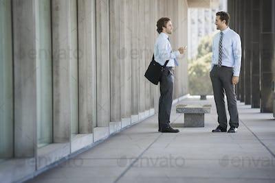 Two businessmen on a walkway outside a building, talking.