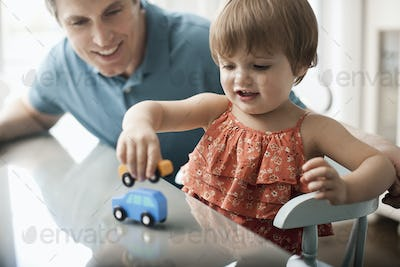A man and a young child sitting playing with toy cars.