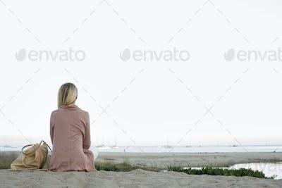 Blond woman sitting on a sandy beach.