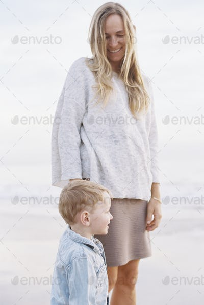 Smiling woman standing on a sandy beach by the ocean with her young son.