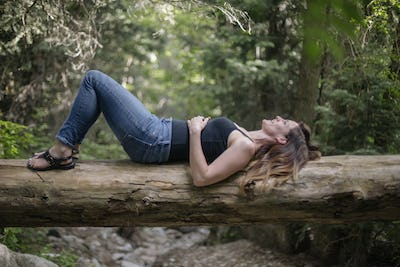 Woman lying on her back on a tree in a forest.