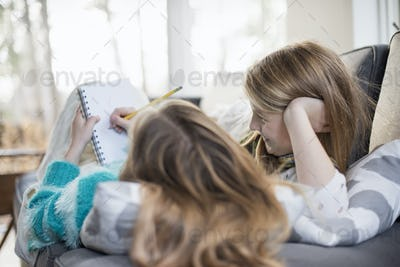 Two girls lying on a sofa, one writing into a notebook with a pencil.