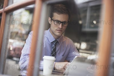 A working day. Businessman sitting  in a cafe, usinga laptop, having coffee.